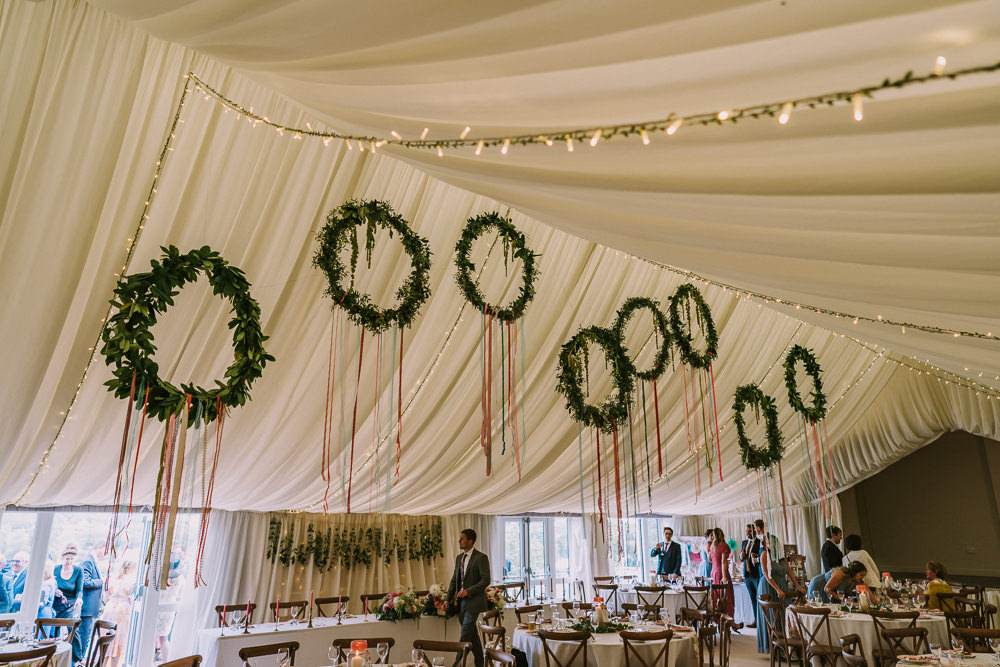Marquee Hanging Wreaths Hoops Suspended Greenery Foliage Ribbon Fairy Lights Crafty Village Hall Wedding Dot and Scolly Photography