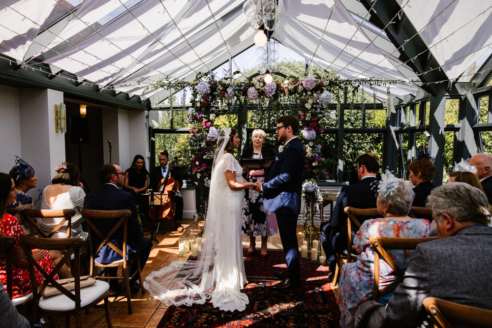 Ceremony Aisle Backdrop Rugs Flowers Flower Arch Conservatory Titchwell Manor Wedding Honey and The Moon Photography
