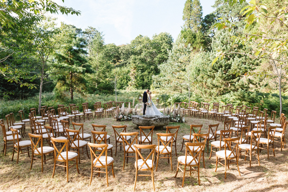 Boconnoc Wedding Debs Alexander Photography Ceremony Woodland Outdoor Circle Round Chairs Flowers Pampas Grass Palm Leaves Dahlias Aisle