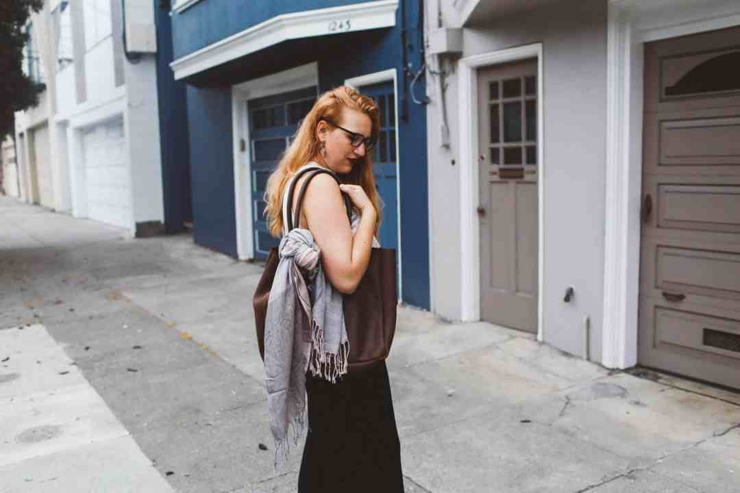 pink scarf black wide leg pants woman red hair leather tote bag