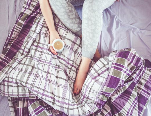 blogging tips woman coffee bed plaid sheets