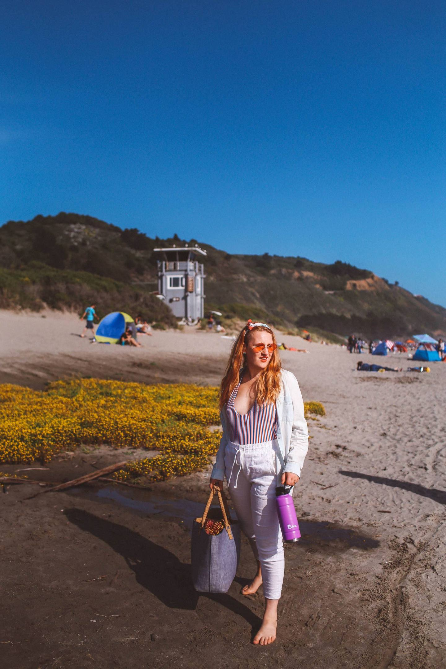 Woman wearing rose colored sunglasses, white pants and a striped swimsuit at Stinson Beach