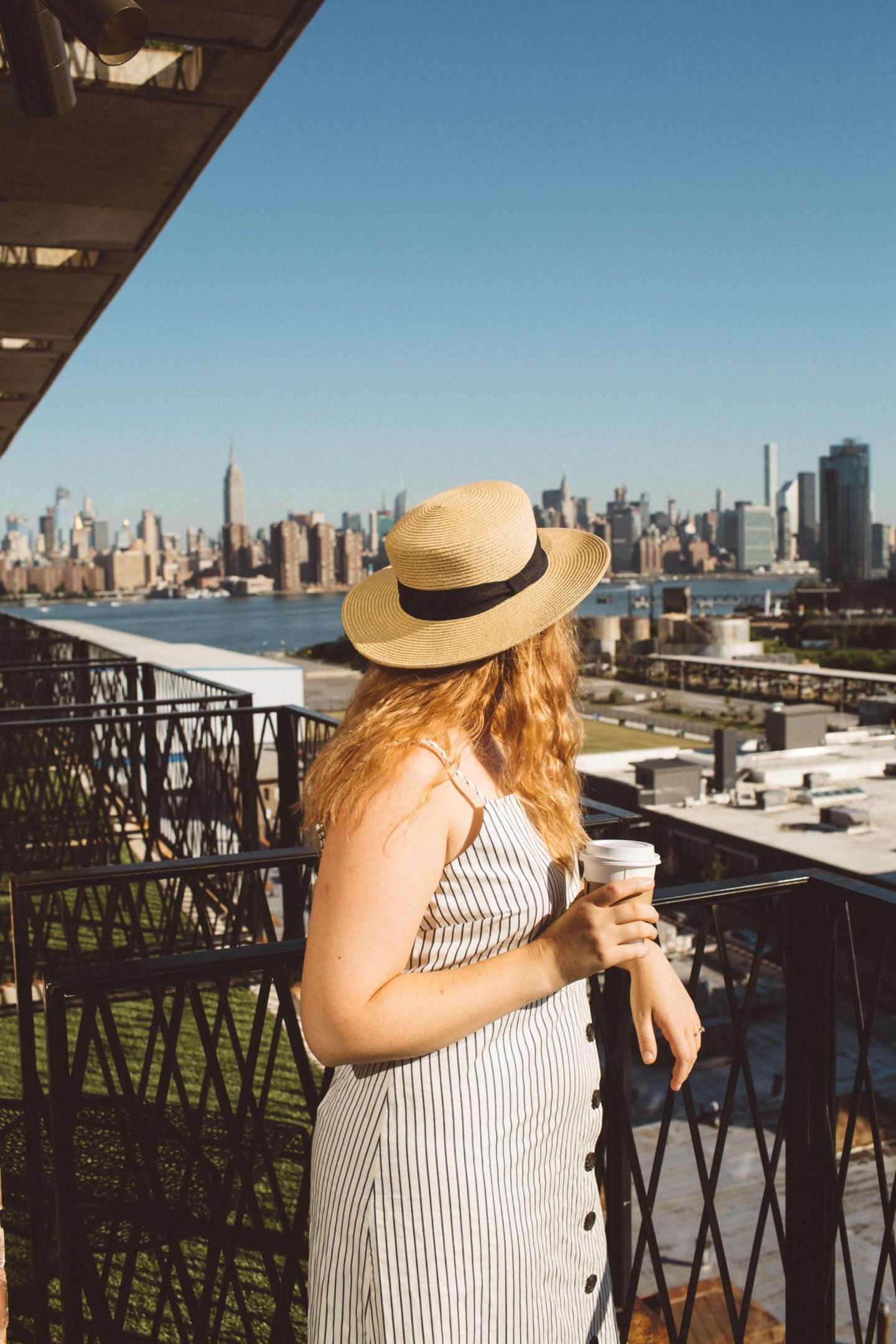 Woman looking at Manhattan from Brooklyn hotel balcony.