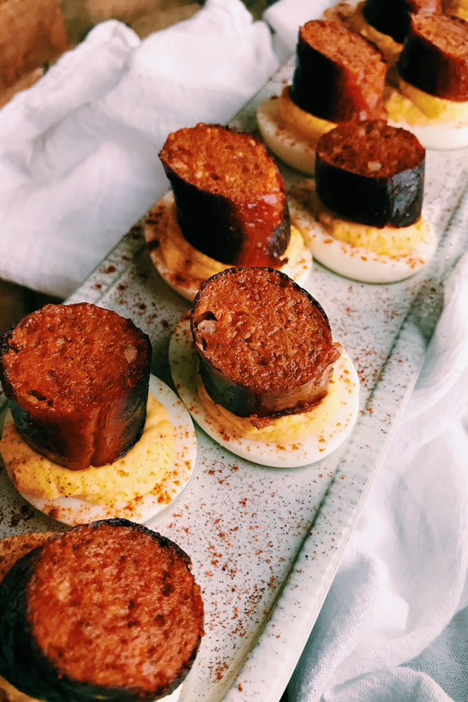 deviled eggs with smoked chorizo links on a white tray