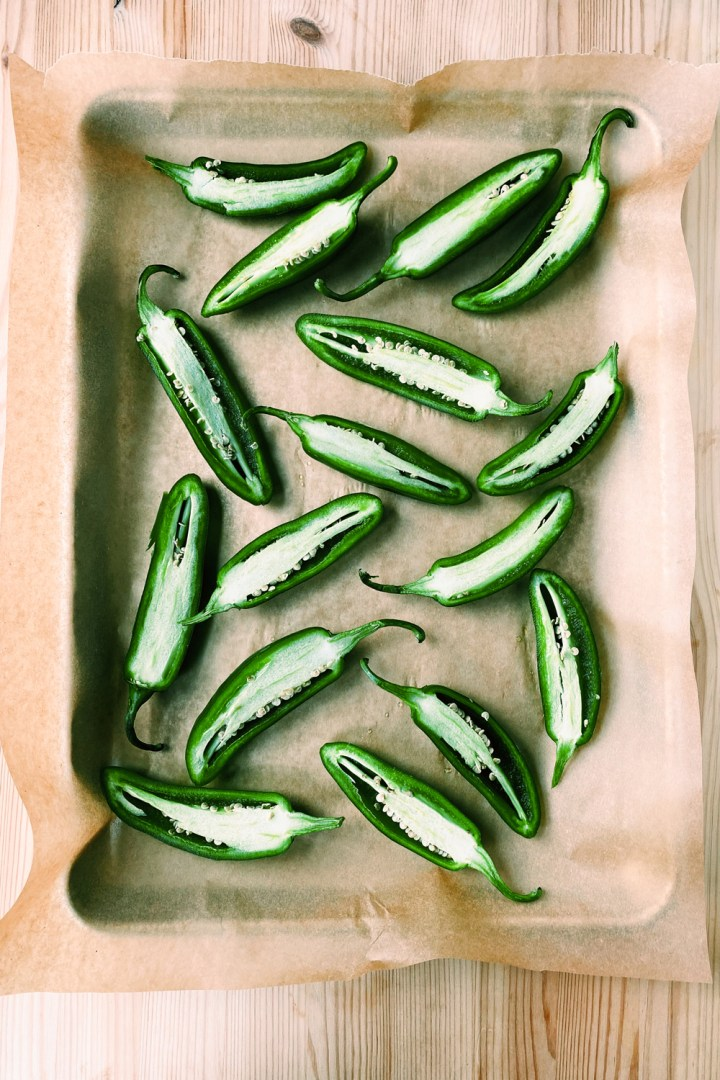fresh jalapeno peppers cut in half on a tray lined with brown paper