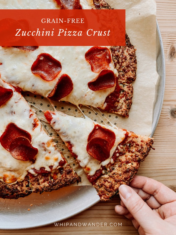 a hand grabbing a slice of pepperoni pizza using zucchini crust off of a pizza pan on a wooden table
