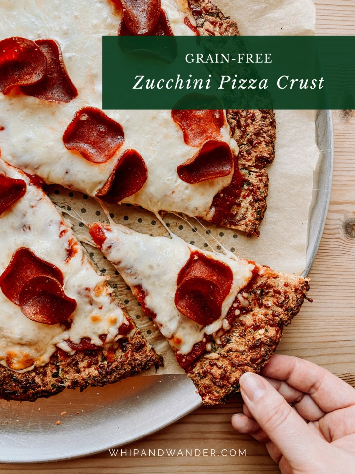 a hand pulling slice of pepperoni pizza on zucchini crust off of a pan resting on a wooden table