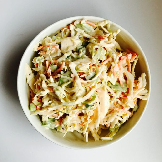 overhead of spicy cabbage slaw in a white bowl on a neutral background