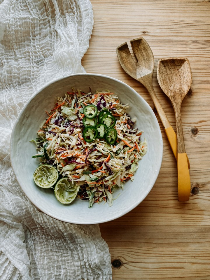 Spicy Cabbage slaw in a white bowl resting on a wooden surface with yellow dipped wooden salad utensils resting next to the bowl