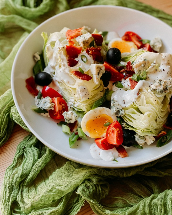 Wedge Salad with Horseradish Blue Cheese Dressing on a deep white plate