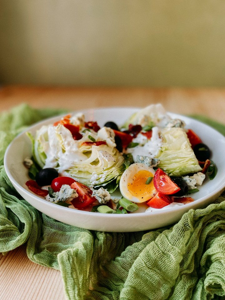 Wedge Salad with Horseradish Blue Cheese Dressing on a green cloth
