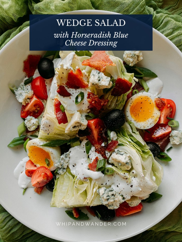 a plate with a large wedge salad with blue cheese horseradish dressing, bacon, tomato, and eggs