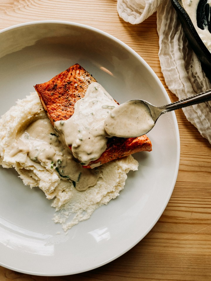 a spoon pouring whisky cream sauce over a piece of salmon and mashed cauliflower