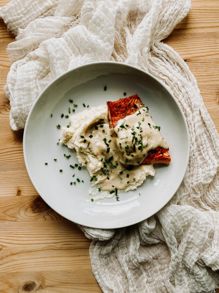 a white dish with salmon mashed cauliflower, and whisky cream sauce resting on a neutral colored fabric on a wooden surface