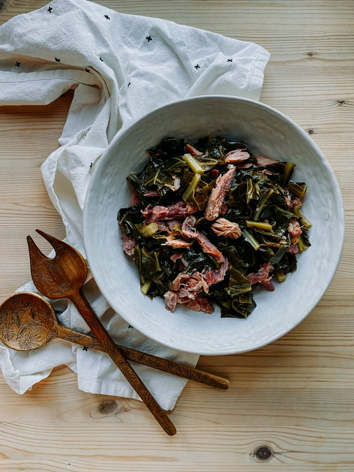 Pressure Cooker Collard Greens with Smoked Ham Hock in a white bowl resting on a white towel on top of a wooden surface with two wooden serving utensils resting nearby