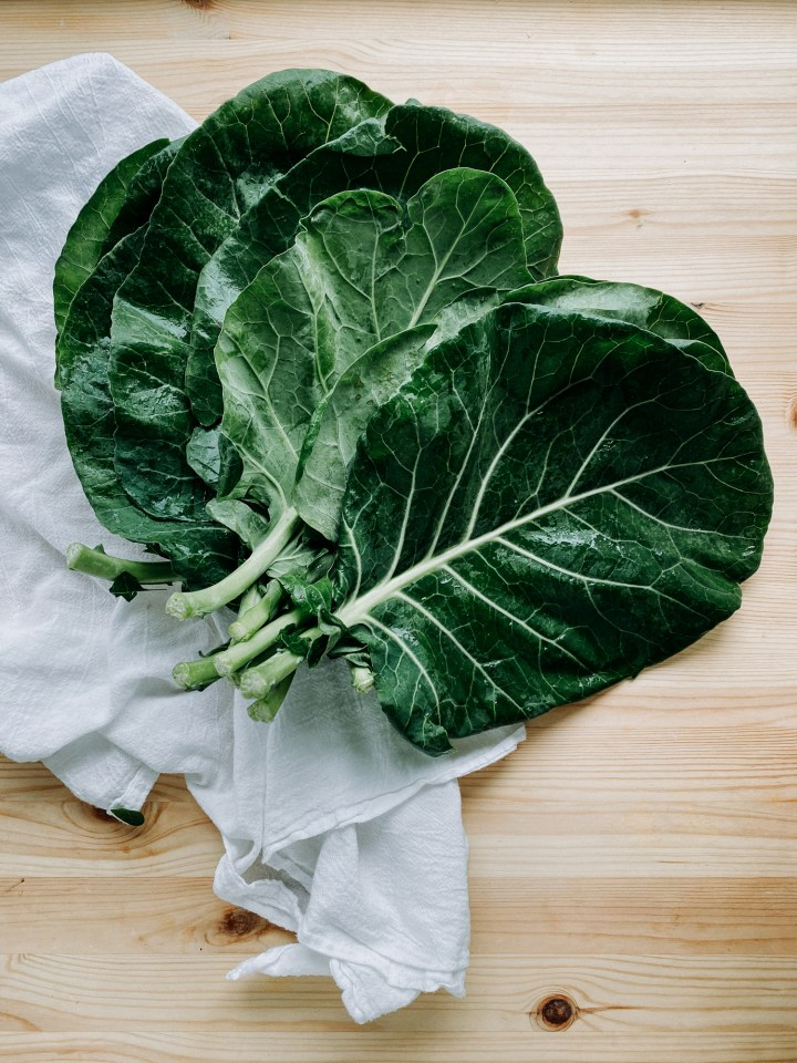 raw collard greens resting on a white towel on a wooden surface