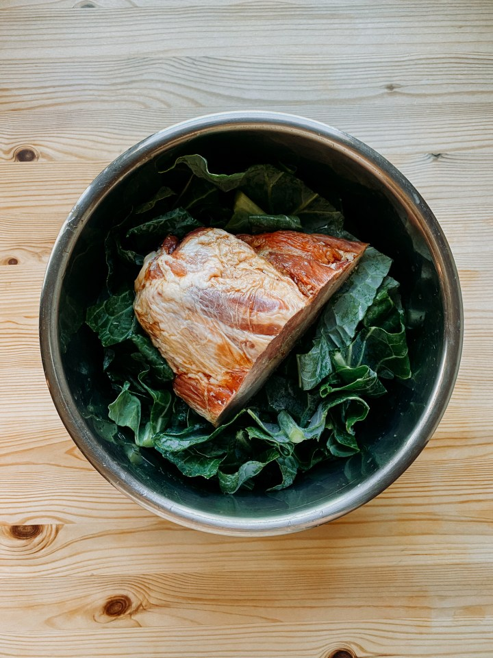 collard greens and a smoked ham hock resting in a metal pot