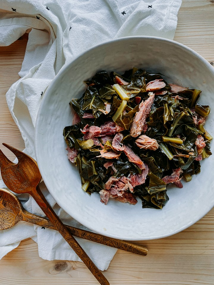 Pressure Cooker Collard Greens with Smoked Ham Hock in a white serving dish with wooden serving utensils resting on a white and black towel nearby