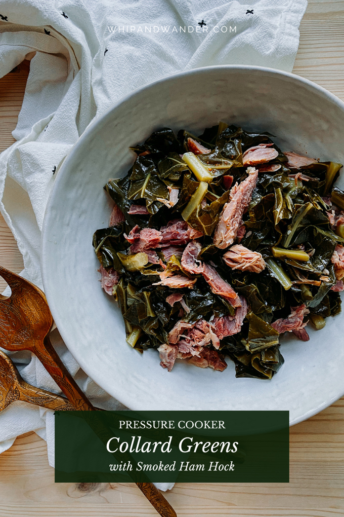 a dish of collard greens with smoked ham hock resting on a towel lined wooden surface with wooden serving spoons nearby