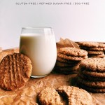 Almond Peanut Butter Cookies stacked next to a glass of milk on a wrinkled parchment paper surface