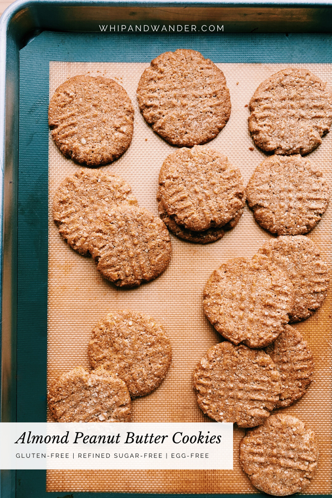 salt topped Almond Peanut Butter Cookies on a silicone baking sheet lined tray