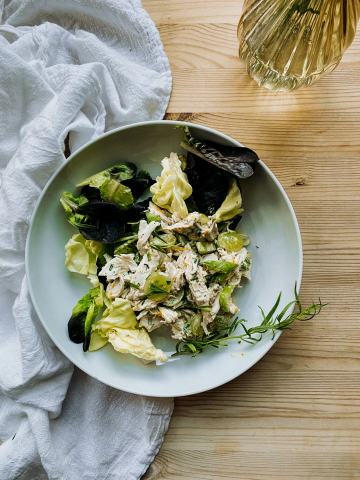 a white bowl filled with butter lettuce, french chicken salad, and a sprig of tarragon resting on a white towel on top of a wooden surface