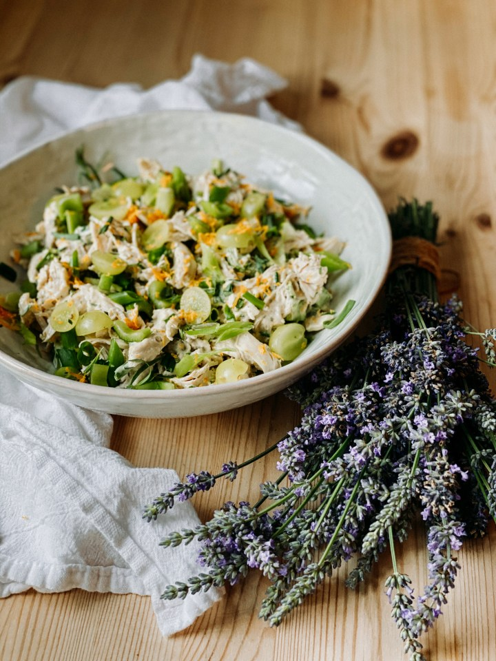 a bundle of lavender in front of a white bowl of french chicken salad with herbs and orange zest