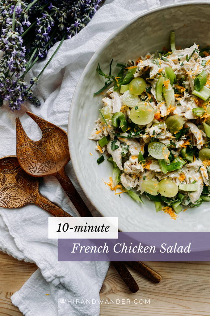 closeup of french chicken salad with lavender and grapes in a white bowl and wooden serving utensils next to the bowl