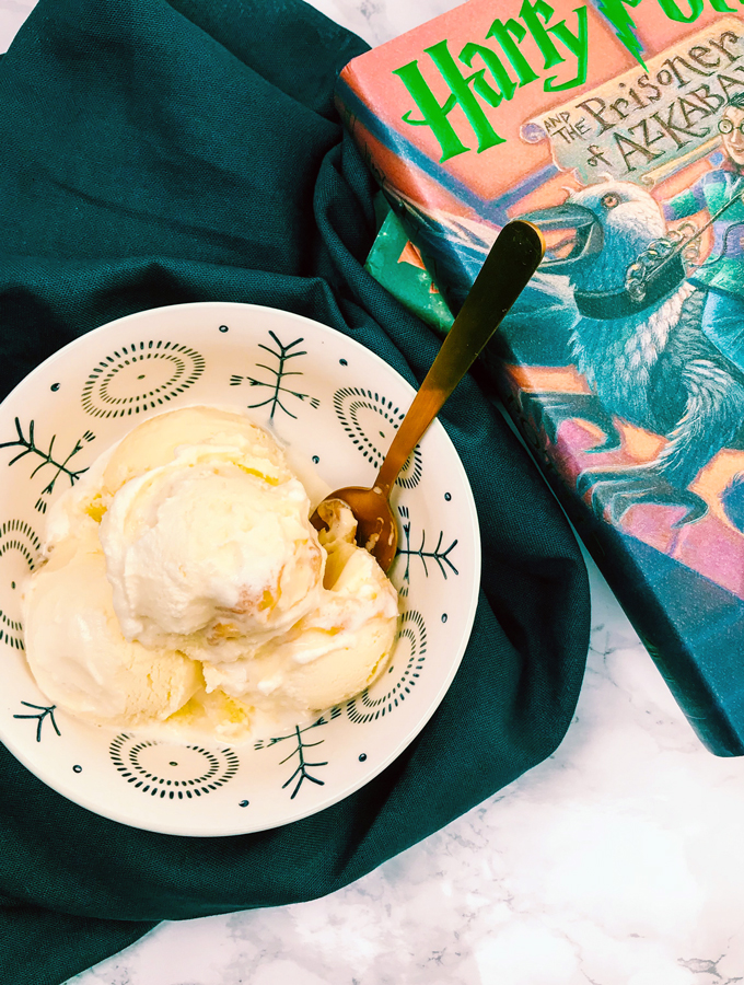 a bowl of frozen custard with a gold spoon and a book next to the bowl