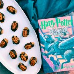 Cockroach Nut Clusters on a white platter with a dark teal towel and a harry potter book