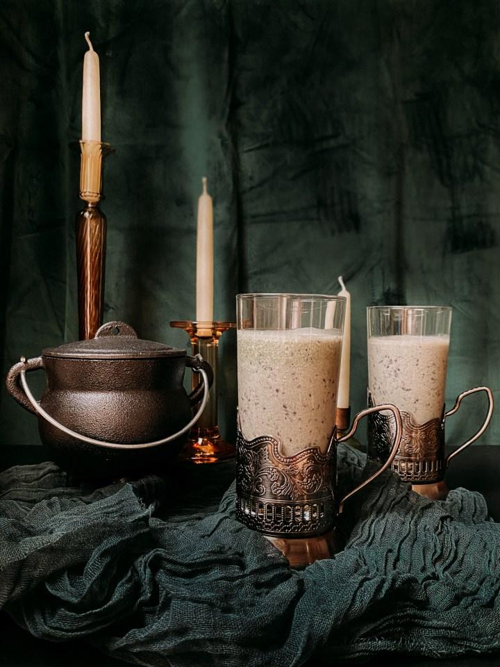 a black cauldron next to two glasses of Polyjuice Potion Smoothie