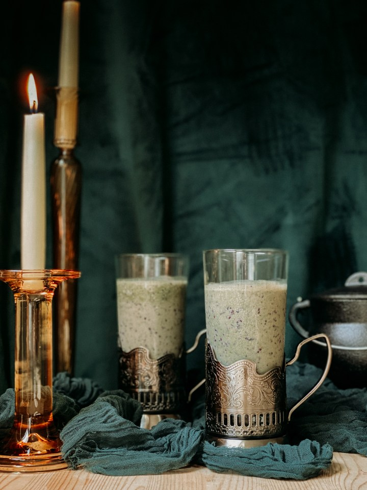 two handled glasses of Polyjuice Potion Smoothie in front of a dark green velvet backdrop