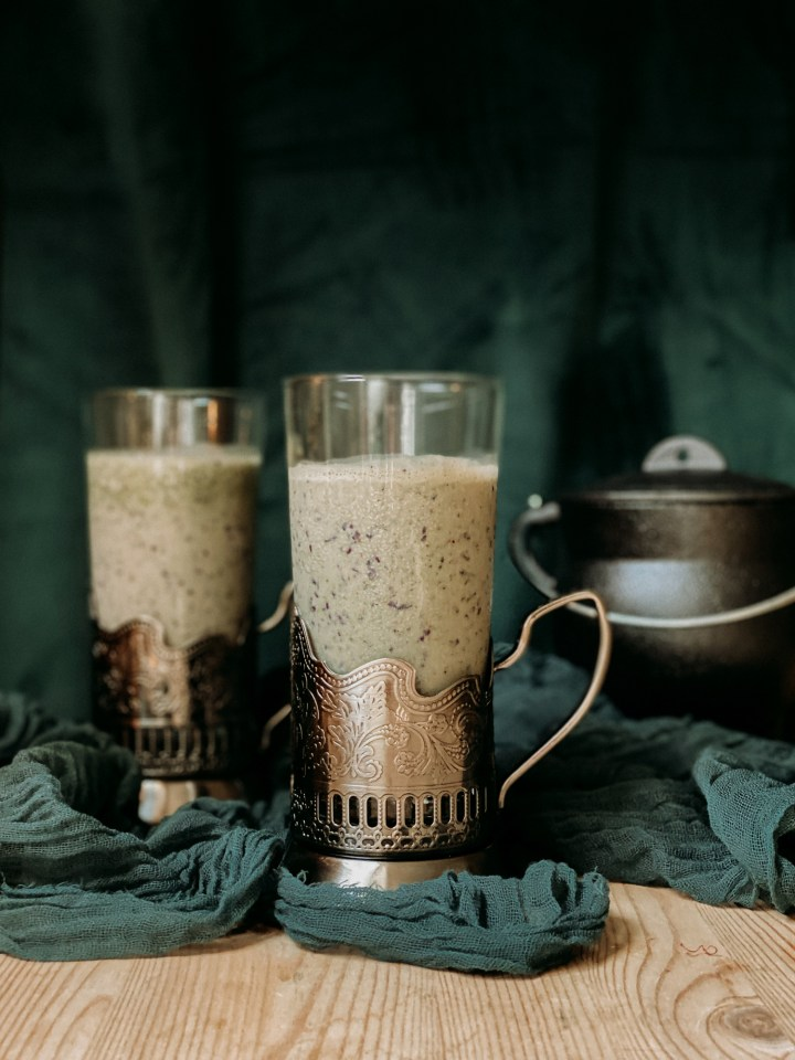 two metal handled mugs of Polyjuice Potion Smoothie on green cloth in front of a dark green background