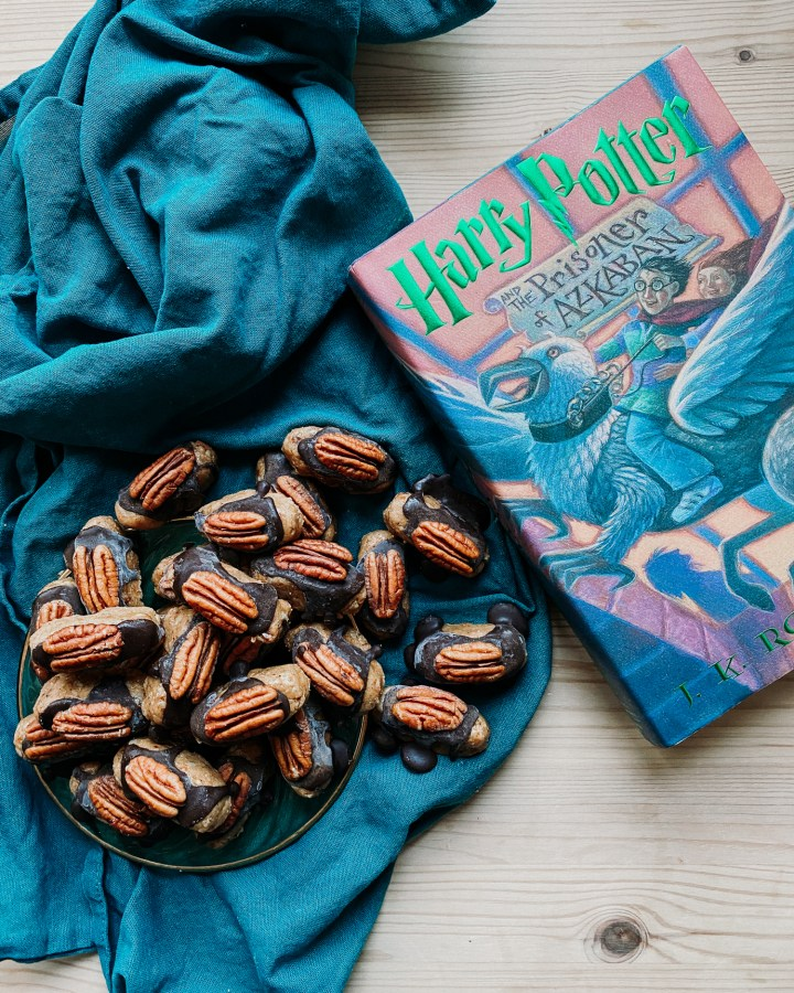 a pile of harry potter inspired cockroach clusters on a green plate resting on a dark teal towel with a harry potter book resting next to the plate