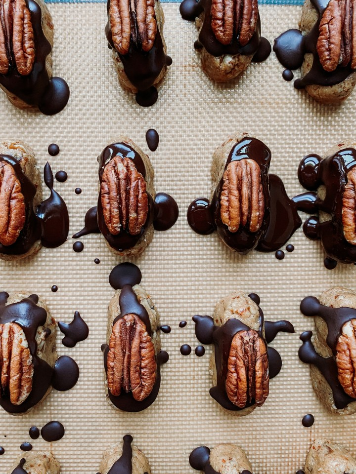 pecan and chocolate topped cockroach clusters on a silicone baking sheet