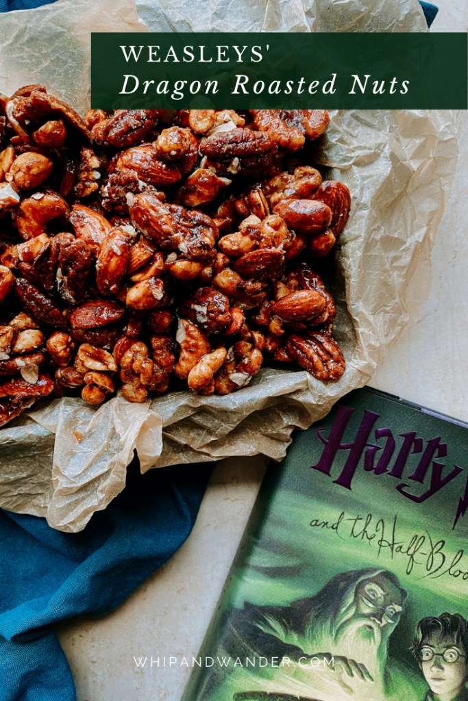 a container of Weasleys Dragon Roasted Nuts beside a green book with purple writing on the title