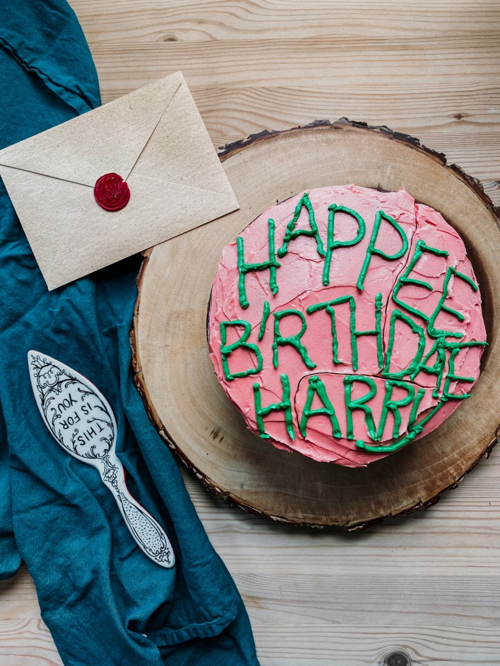 a pink frosted cake that says hapee birthdae harry in green icing sitting on a tree stump with a dark blue green towel, a cake server, and an envelope