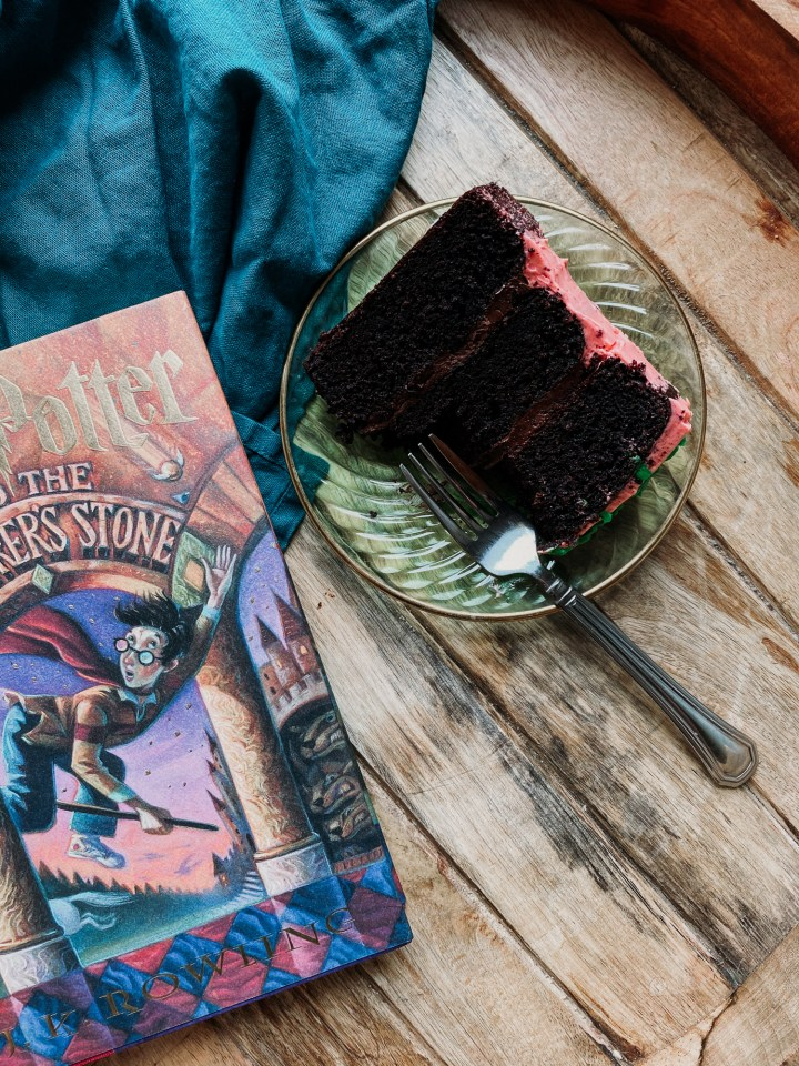 a green glass plate with a slice of chocolate cake and a fork sitting next to a harry potter book on a wooden surface
