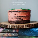 a stack of harry potter books with a big gluten-free chocoalte birthday cake frosted in pink icing