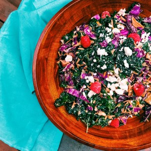 kale salad with raspberries and feta cheese in a large wooden bowl with a teal towel