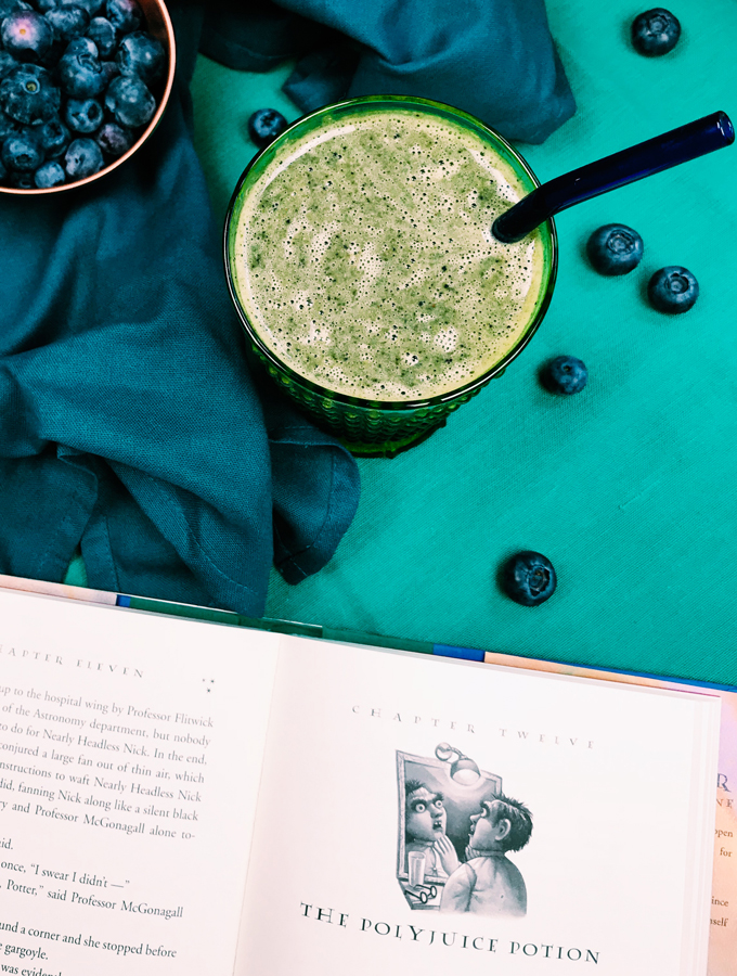 green smoothie in a green glass with a teal background and an open book