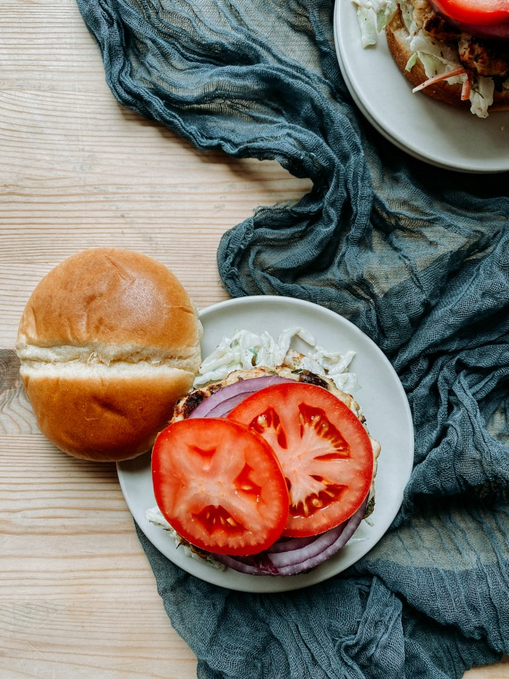 a tomato and red onion topped burger on a light colored plate resting on a dark teal cloth