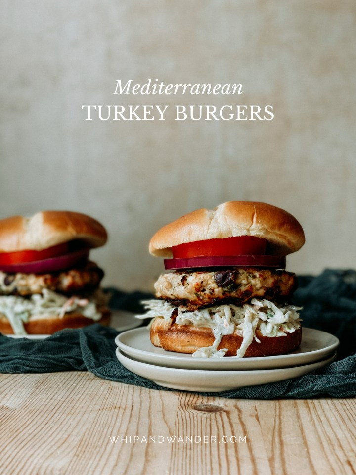 two Mediterranean Turkey Burgers with brioche buns on plates