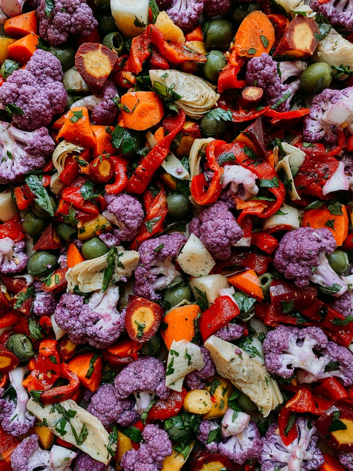 a closeup of peppers, olives, carrots, cauliflower
