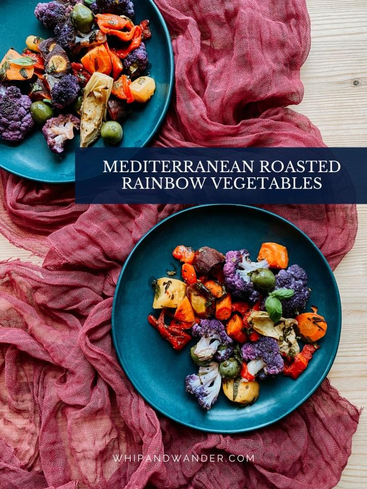roasted rainbow vegetables on two dark teal plates on a maroon cloth