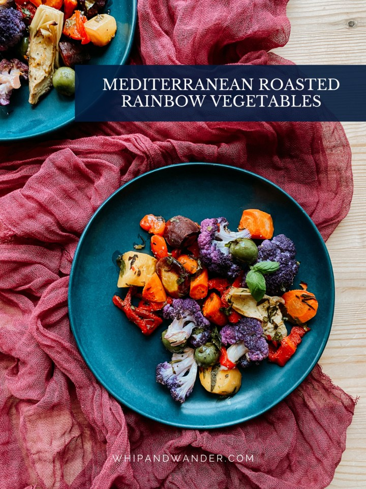 a dark teal plate with Mediterranean Roasted Rainbow Vegetables resting on a dark red cloth