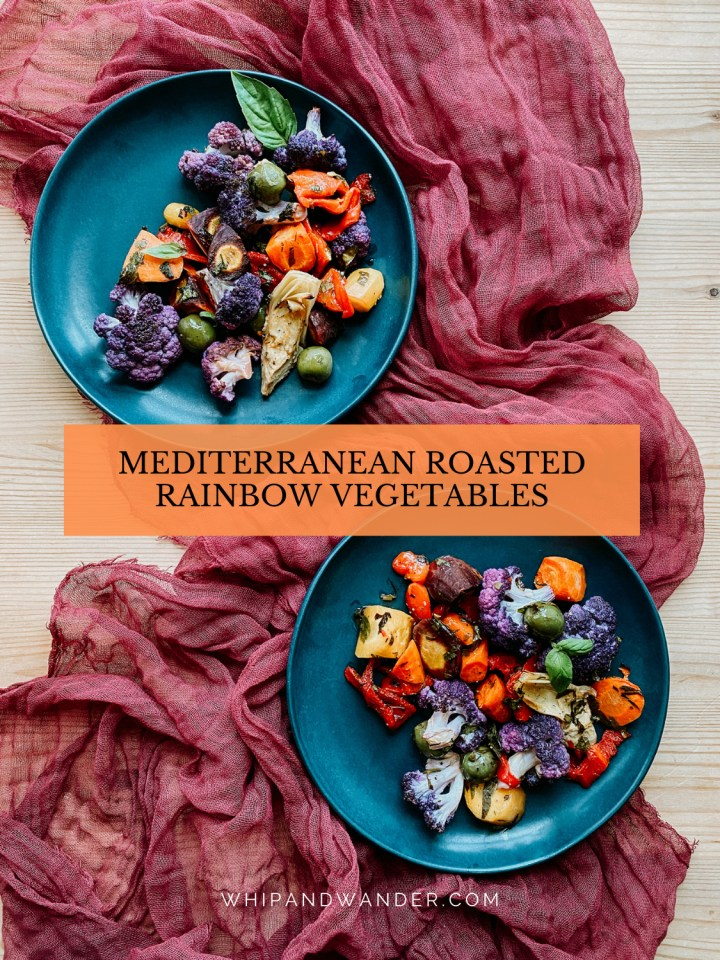 a dark red cloth with two blue plates containing Mediterranean Roasted Rainbow Vegetables