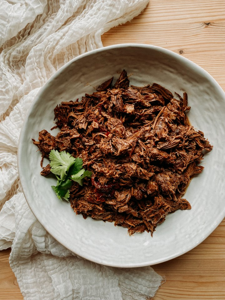 a white dish filled with Pressure Cooker Barbacoa Beef and cilantro on a piece of white cloth on wooden table
