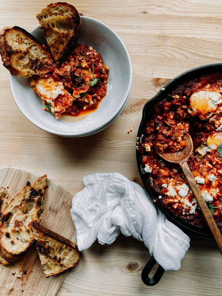 a cast iron skillet with shakshuka resting next to a white bowl with shakshuka and toast in it and a wooden cutting board with toast resting on the board