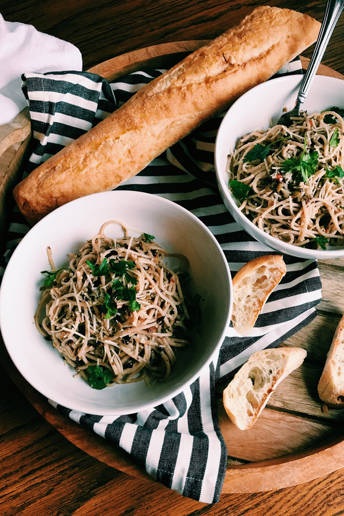 Pasta with Olive Tapenade in white bowls with a baguette and sliced bread on a striped towel